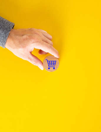 Male hand placing a blue shopping cart icon on yellow background. Shopping or online e-commerce concept.