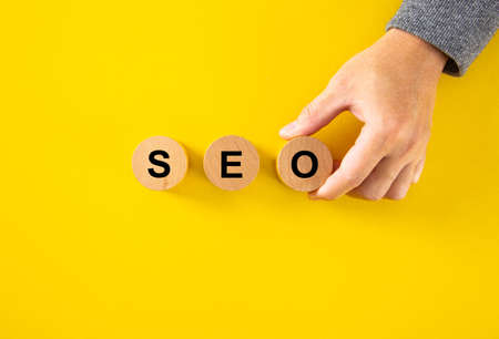 SEO (Search Engine Optimization) text wooden cube blocks on yellow background. Idea, Strategy, marketing, Keyword and Content concept