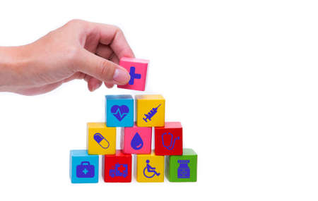 Hand chooses a emoticon icons healthcare medical symbol on wooden block , Healthcare and medical Insurance concept