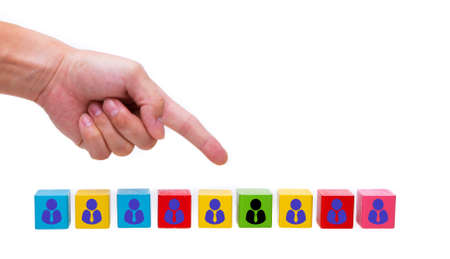 Hand pointing at a wooden block one leader person represented by icon. Leader stands out from crowd.