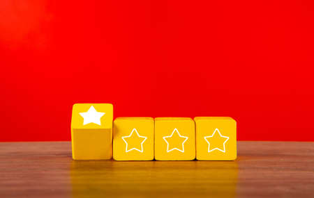 Wooden cubes with one stars out of four. Concept of poor service rating and evaluation.