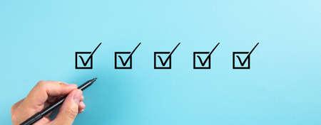 Close-up, Hand holding black pen checking mark on check boxes. Survey Conceptual
