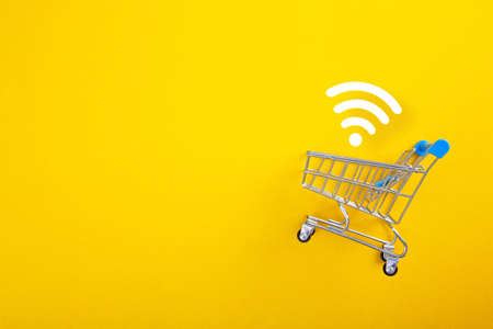 close-up of shopping trolley with wifi signal on yellow background with copy space