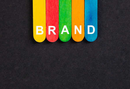 Business concept.Text BRAND writing on colored sticks on wooden background.
