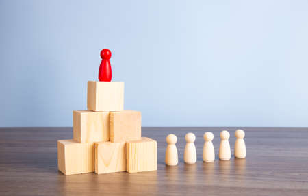 Career growth, development. Leadership, goal achievement. Wooden people figures on top of wooden blocks