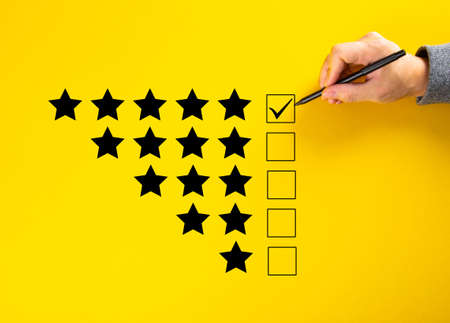 Hand putting a check on the 5 star rating. Survey Concept