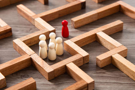 Leadership concept.Wooden miniature at the start point of puzzle maze wood block 免版税图像