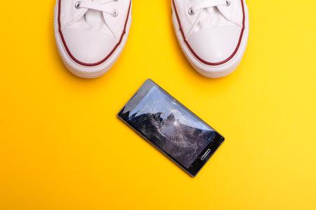 Mobile phone with broken screen on floor Foto de archivo