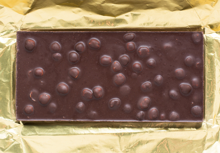 nuts: Chocolate bar with nuts in open gold foil wrapping