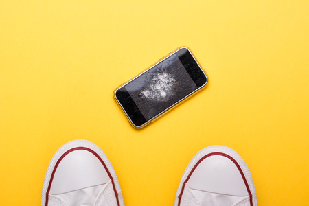 Mobile phone with broken screen on yellow floor Stock Photo