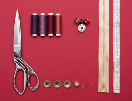 Sewing tools on red background