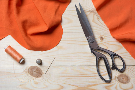 taylor: Cutting textile or fine cloth with a taylor scissors on wooden table. Sewing tools Stock Photo