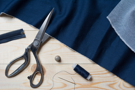 Cutting textile or fine cloth with a taylor scissors on wooden table. Sewing tools Imagens