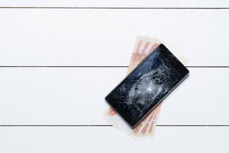 Mobile phone with broken screen and money on repair on wooden floor Stock Photo
