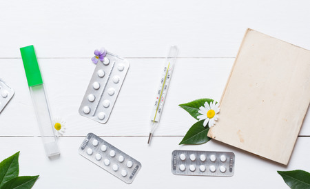 fever plant: Thermometer and pills on white wooden table flat lay
