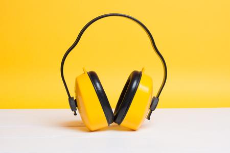 黄色の保護のヘッドフォンを黄色の背景に取り組んで