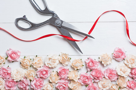 Grand opening concept with scissors cutting red ribbon on white wooden background with roses on it
