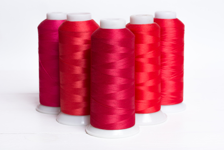 Red bobbin thread on white wooden table background