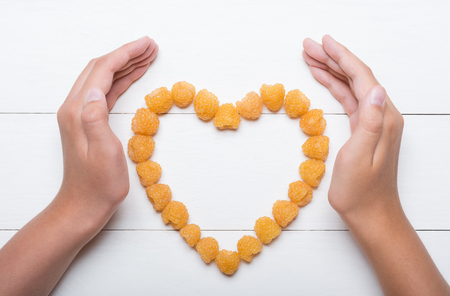 hands holding heart: Young hands holding heart made of yellow raspberries concept Stock Photo