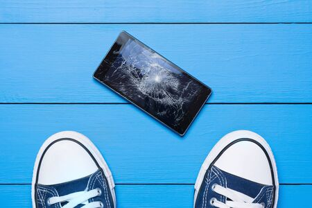 Mobile phone with broken screen on floor concept Stock Photo