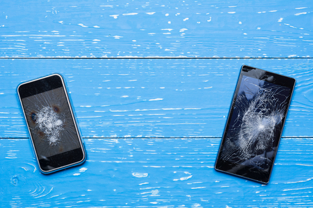 Two broken mobile phones on vintage painted wooden table Stock Photo