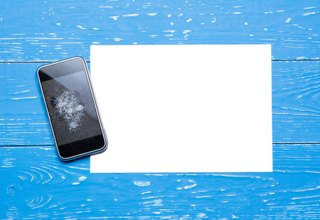 Broken mobile phone with paper sheet on vintage painted wooden table Stock Photo