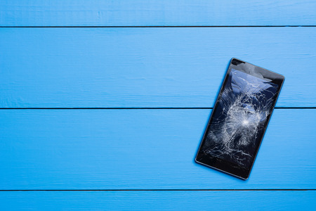 Broken mobile phone on painted wooden table background
