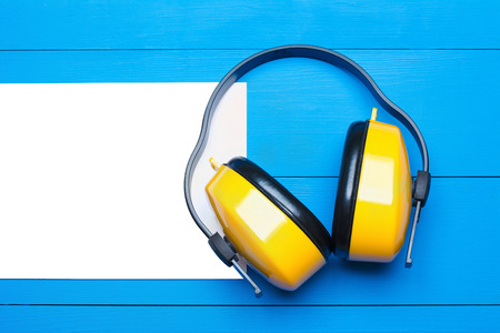Yellow working protective headphones on blue wooden table background