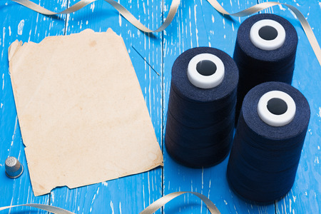 bobbin: Blue bobbin thread and vintage paper sheet. Copy space Stock Photo