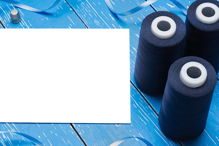 bobbin: Blue bobbin thread and paper sheet. Copy space