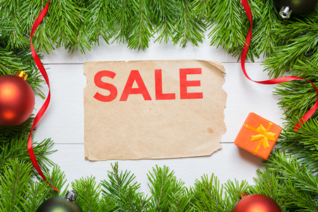 Sale concept. Christmas fir tree and aged paper sheet Imagens