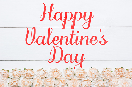 Happy Valentines Day painted on white wooden desk. Roses pattern
