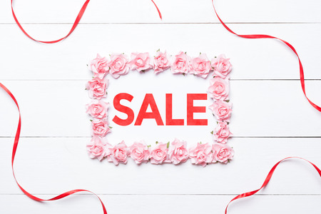 Sale concept in frame made of roses with red ribbon