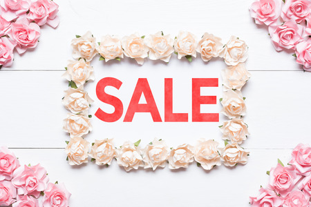 Sale concept. White frame made of roses over wooden table