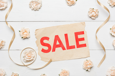 Word Sale on vintage paper sheet and roses on white