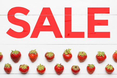 Word Sale painted on white wooden desk. Strawberry pattern