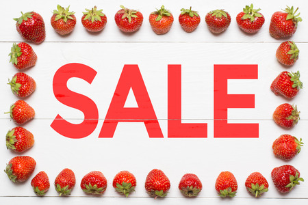 Word Sale painted on white wooden desk. Strawberry frame