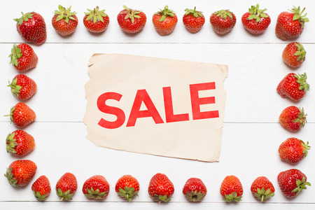 Strawberry frame and vintage paper sheet. Sale concept