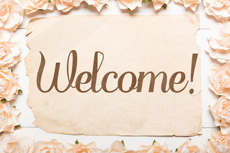 Word Welcome. White roses frame and paper sheet