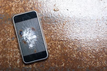 Broken Phone with cracked screen on wet metal background Stock fotó