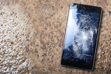 Broken Phone with cracked screen concept  on wet concrete