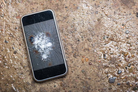Broken Phone with cracked screen on wet concrete