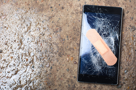 Broken Smart Phone with cracked screen fixed with plaster. Concept