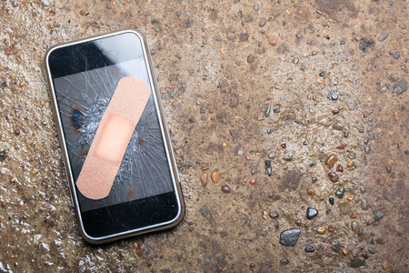 Broken Smart Phone with cracked screen fixed with sticking plaster