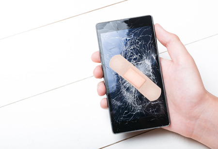 Mobile Smart Phone with cracked screen with plaster in hand