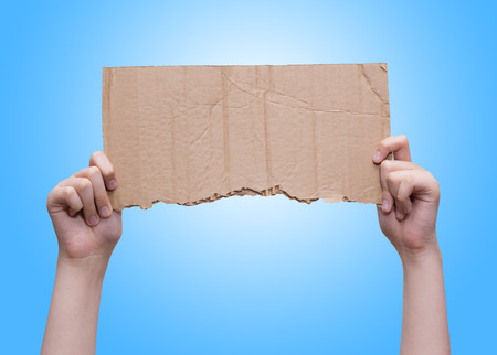 Hands holding empty torn piece of cardboard over blue background Imagens