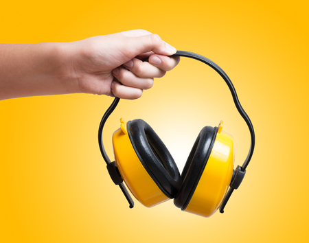 Yellow protective ear muffs in hand