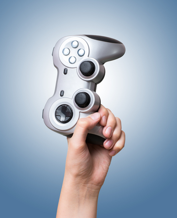 Game controller in hand raised up over blue background