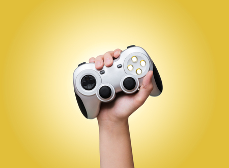Game controller in hand raised up over yellow background Imagens