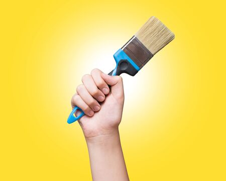 Flat brush in hand raised up over yellow background